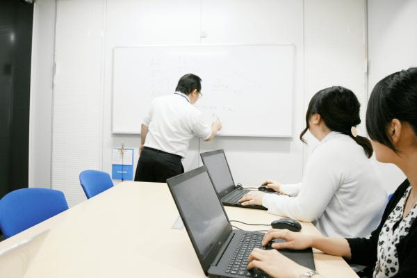 本社の会議室で、IT業界についての講義を行う上司と、研修を受ける女性社員
